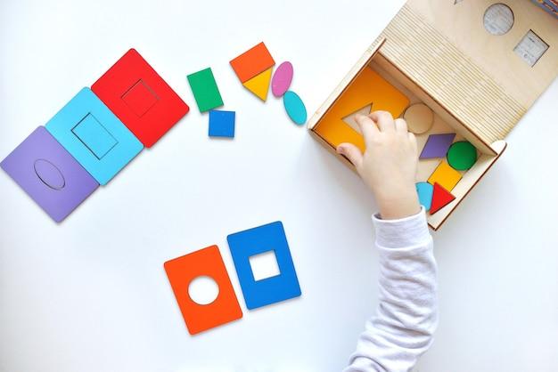 Aprendendo cores e formas. a criança recolhe um classificador brinquedos de lógica educacional para crianças