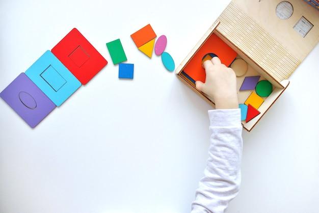 Aprendendo cores e formas. brinquedo infantil de madeira. a criança coleta um classificador. brinquedos lógicos educativos para crianças.