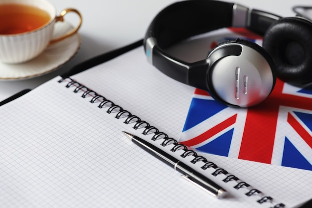 Aprendendo idiomas extrangeiros. bloco de notas para entradas e uma bandeira. cursos de idiomas, audição de áudio.