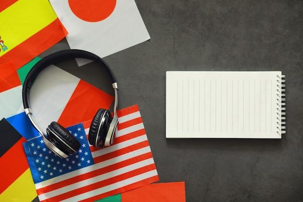 Aprendendo idiomas extrangeiros. cursos de idiomas em áudio. plano de fundo de bandeiras de países e fones de ouvido na mesa.