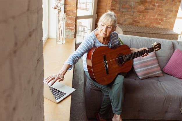 Aprender a tocar violão online. mulher sênior estudando em casa, fazendo cursos online