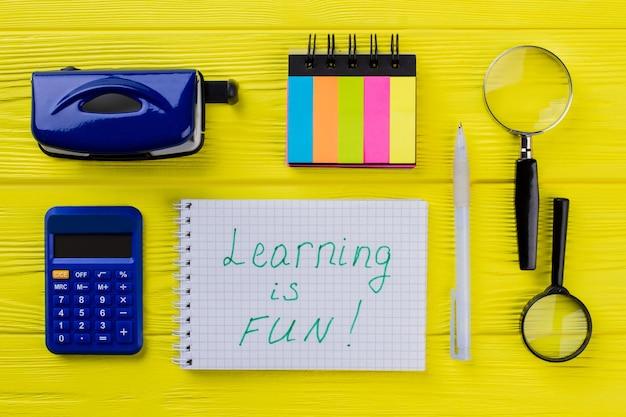 Aprender é divertido. artigos estacionários planos leigos para educação na mesa de madeira amarela.