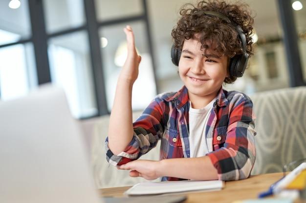 Aprender é divertido garotinho latino-americano curioso usando fones de ouvido e um laptop enquanto estuda na