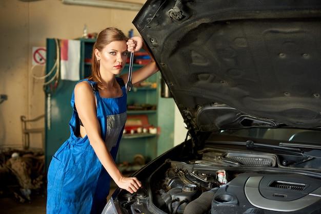 Aprendiz fêmea está ao lado de carro, segura a chave na mão