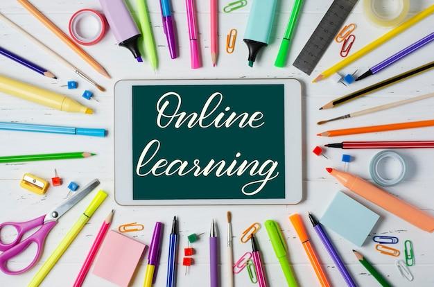 Aprendizagem online - inscrição manuscrita em um tablet. o conceito de treinamento à distância para crianças. tablet e material de escritório em um fundo branco de madeira.