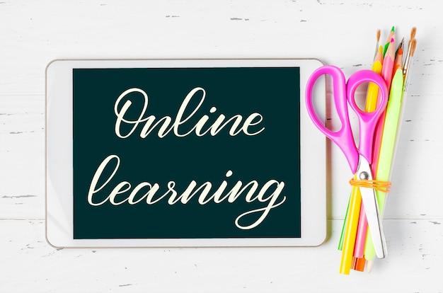 Aprendizagem online - inscrição manuscrita em um tablet. o conceito de treinamento à distância para crianças.