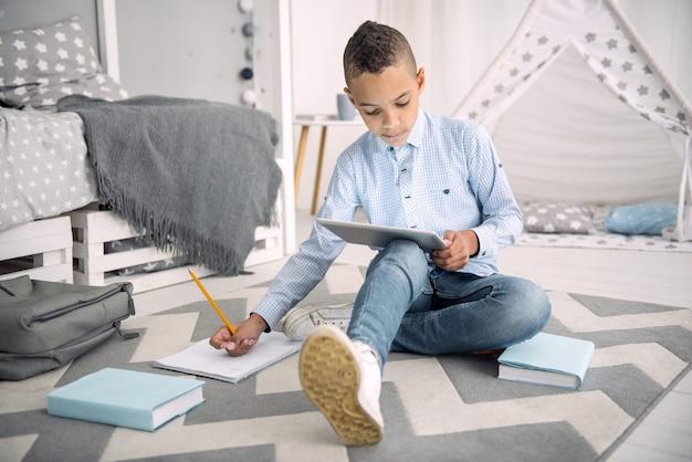 Aprendizagem online. rapaz afro-americano focado realizando tarefas ao usar o tablet