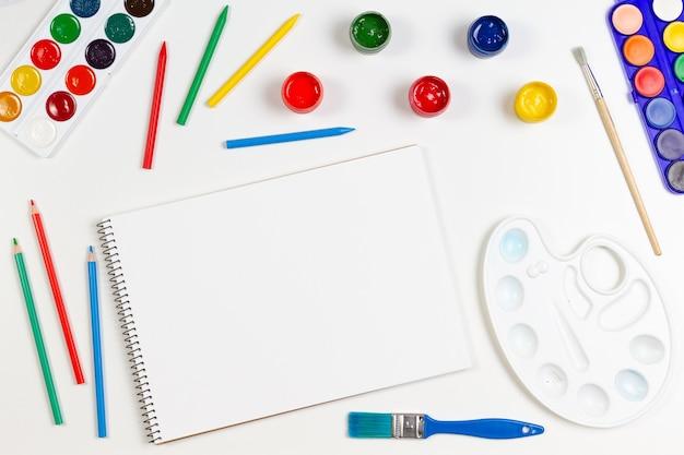 Aprendizagem, passatempo, fundo de arte. caderno de desenho vazio com material de arte ao redor. brincar. vista superior, configuração plana