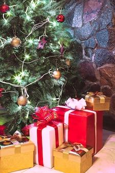 Apresenta caixas embaixo da árvore de natal. cores dourado, vermelho e branco