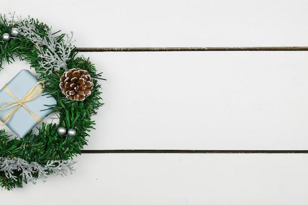 Apresenta com um ramo de pinheiro e decorações em um fundo de tábuas de madeira brancas
