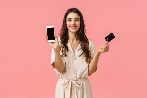 Apresenta, conceito de compras e beleza. moda jovem em vestido moderno, segurando o smartphone e cartão de crédito, sorrindo alegremente, encomendar produto on-line, rosa de pé
