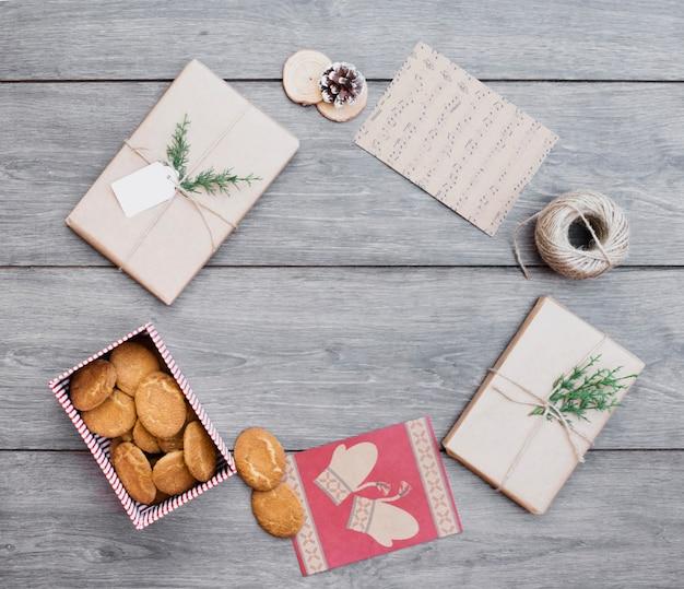 Apresenta perto de biscoitos em caixa, cartões postais e bobina de fio