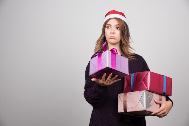 Apresenta-se jovem mulher com chapéu de papai noel segurando caixas de presente.