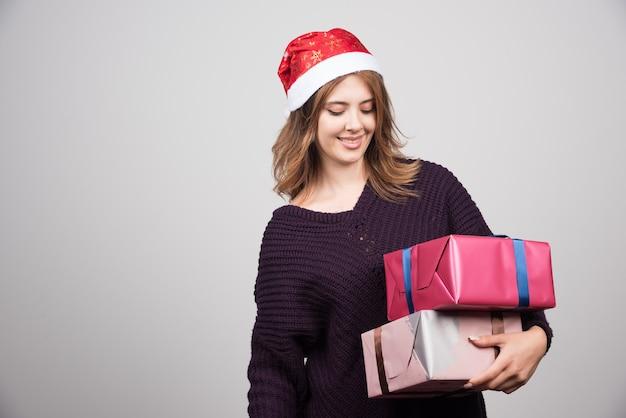 Apresenta uma jovem mulher feliz com chapéu de papai noel segurando caixas de presente.