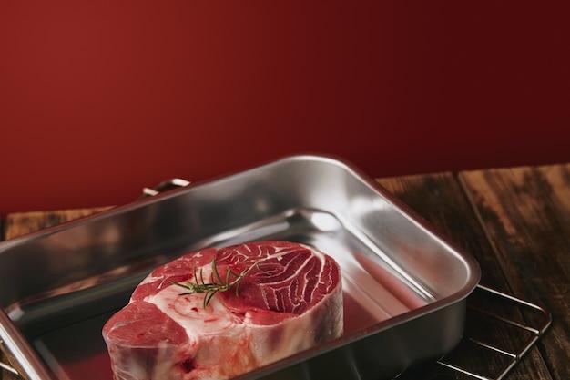Apresentação de bife de perna angus cru em uma panela de aço prata sobre fundo vermelho de mesa de madeira