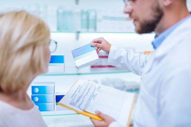 Apresentação de comprimidos. mulher loira atenta olhando para a prateleira e sendo em todos os ouvidos