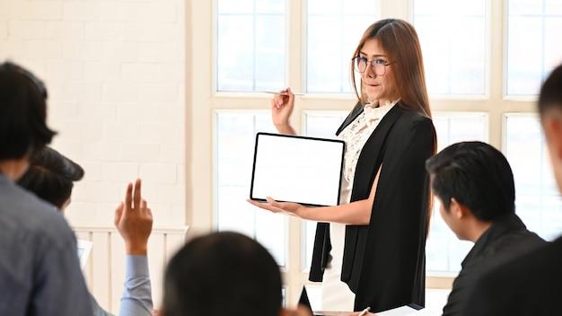 Apresentação de empresária com tablet tela vazia na sala de reuniões.