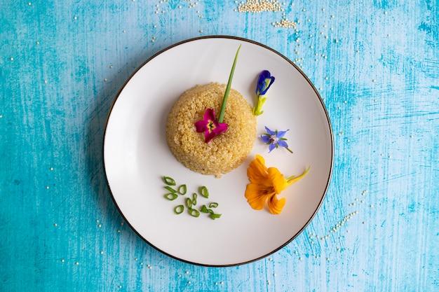 Apresentação de prato de quinoa decorada com flores comestíveis