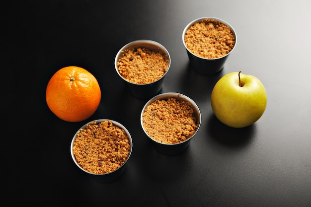 Apresentação de quatro xícaras idênticas de aço inoxidável com sobremesa crumble de maçã, uma laranja e uma maçã amarela atiradas de cima para baixo na mesa preta