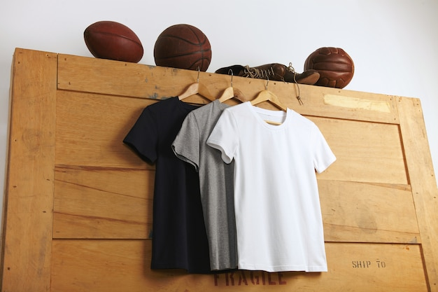 Apresentação de uma camiseta de manga curta lisa branca, cinza e preta com futebol, basquete e vôlei vintage e velhas botas esportivas de couro em cima de uma caixa de transporte de madeira