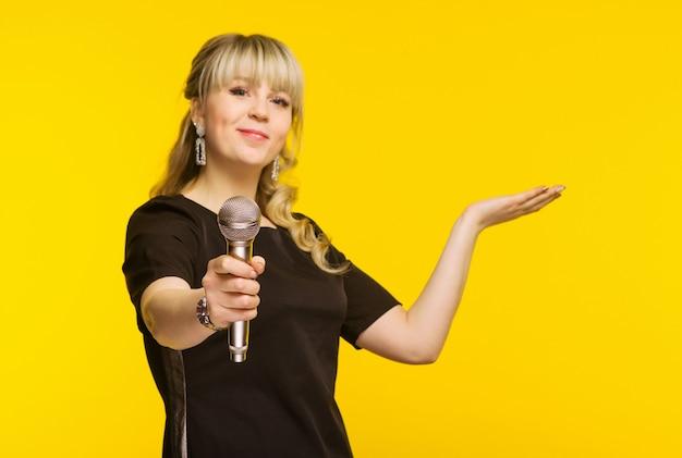 Apresentação, discurso público, conferência, radiodifusão, publicidade. alegre jovem empresária, repórter, apresentador de tv segurando um microfone isolado fundo amarelo brilhante. foco no microfone
