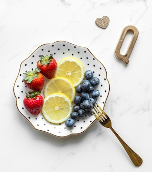 Apresentação feminina e feminina de prato de frutas coloridas