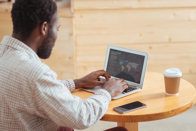 Apresentação informativa. jovem trabalhador sentado à mesa do café e criando uma apresentação sobre as transferências do comércio global em seu laptop