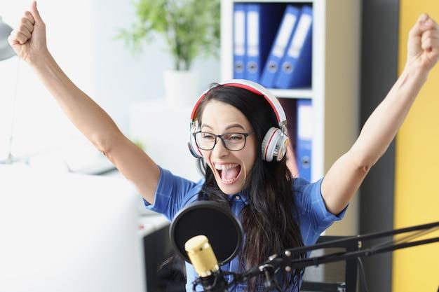 Apresentador alegre e entusiasmado com fones de ouvido e microfone olhando para esportes no monitor do computador