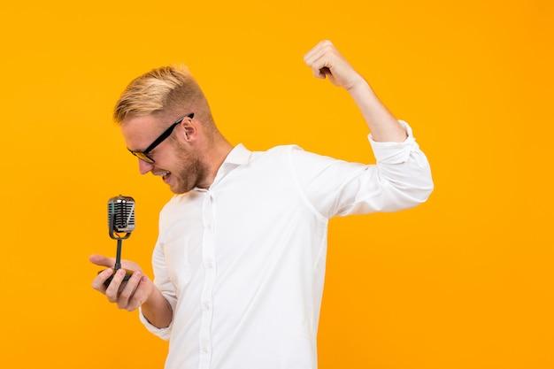 Apresentador bonito em uma camisa branca com um microfone retrô canta no amarelo