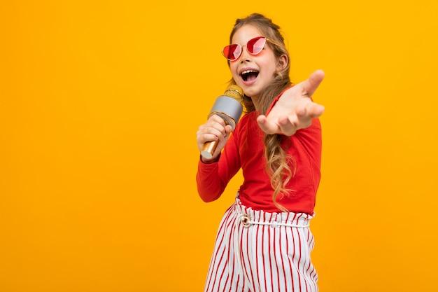 Apresentador com um microfone em um fundo amarelo