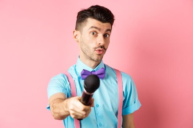 Apresentador de programa masculino bonito estende a mão com o microfone, pedindo entrevista ou comentários, de pé sobre um fundo rosa.