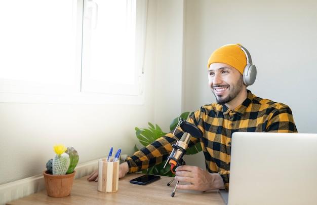 Apresentador de rádio sentado em um escritório bem iluminado
