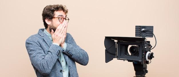 Apresentador de televisão parecendo feliz, alegre, sortudo e surpreso cobrindo a boca com as duas mãos