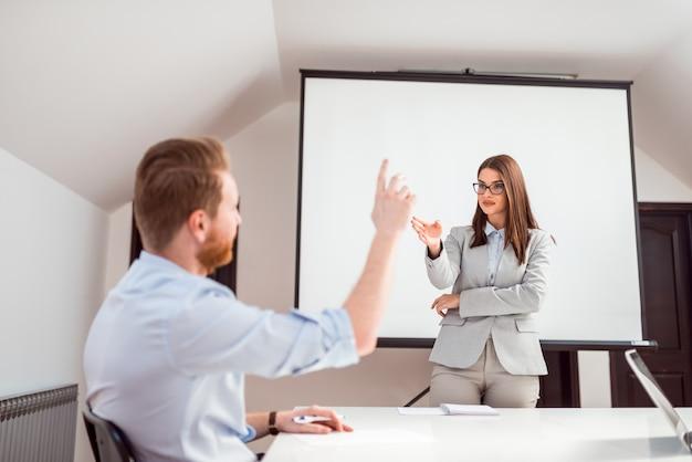 Apresentador fêmea que faz a pergunta e um homem que levanta a mão para responder.