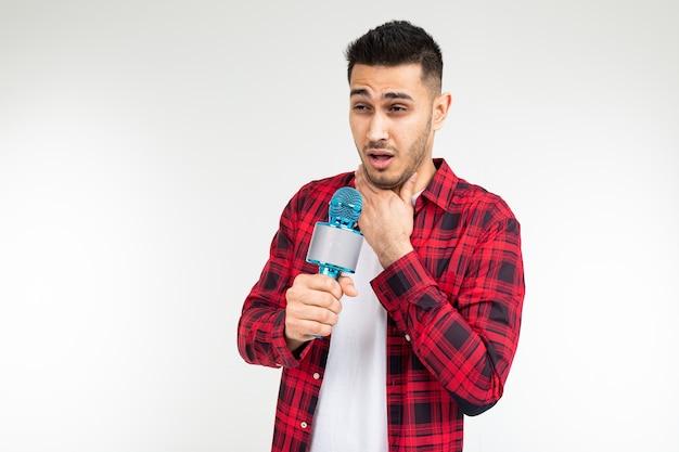 Apresentador masculino com um microfone nas mãos tem dor de garganta em um fundo branco de estúdio isolado.