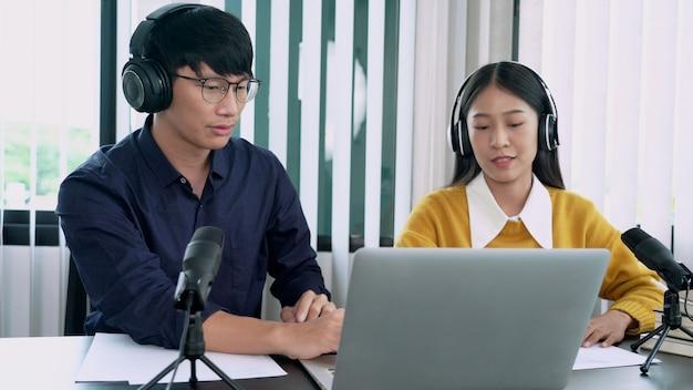 Apresentadora de rádio asiática entrevistando um convidado do sexo masculino na estação de rádio