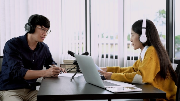 Apresentadora de rádio asiática gesticulando para o microfone enquanto entrevistava um homem convidado na estação de rádio durante um programa de rádio ao vivo no estúdio.