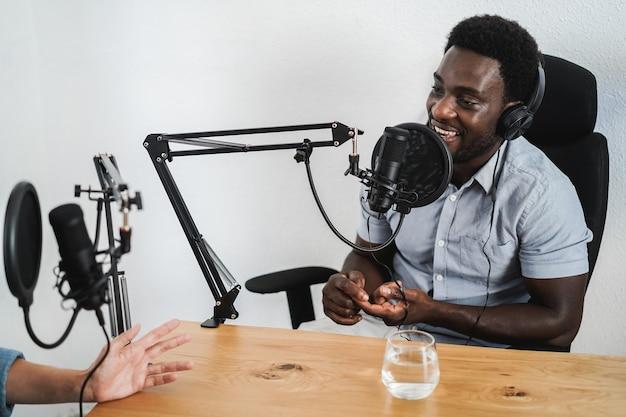 Apresentadores fazendo sessão de podcast juntos - orador africano dando uma entrevista durante a transmissão ao vivo - foco no rosto
