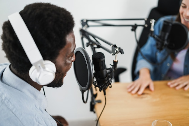 Apresentadores fazendo uma sessão de podcast juntos - locutora fazendo uma entrevista durante a transmissão ao vivo - conceito de tendências de tecnologia - foco no rosto do homem certo