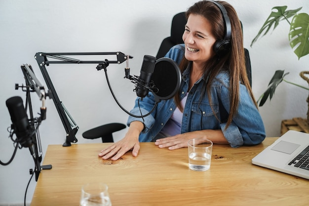 Apresentadores fazendo uma sessão de podcast juntos - locutora fazendo uma entrevista durante a transmissão ao vivo - foco principal no microfone