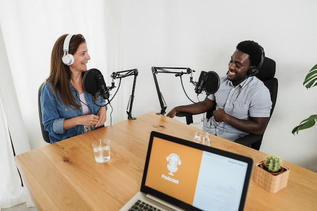 Apresentadores multirraciais transmitindo podcast juntos em estúdio doméstico - foco no rosto da mulher