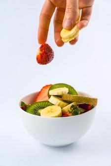 Apresentando ingredientes de cima com a mão de uma mulher, receita para uma salada de frutas com kiwis, morangos, bananas