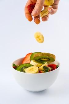 Apresentando os ingredientes de cima, receita para uma salada de frutas com kiwis, morangos, bananas