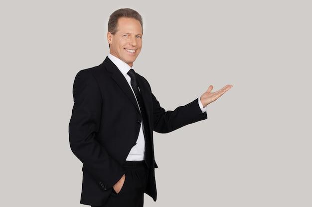 Apresentando seu produto. homem maduro alegre em trajes formais apontando para longe e sorrindo em pé contra um fundo cinza