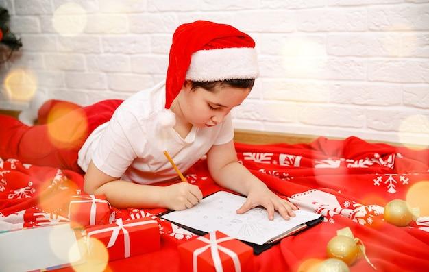 Apresentar lista de desejos feliz ano novo criança menino escrevendo carta para o papai noel