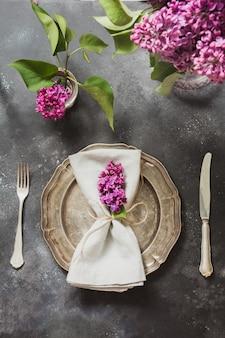 Apresente o ajuste de lugar com as flores lilás cor-de-rosa, pratas no fundo do vintage.