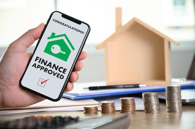 Aprovação de empréstimo hipotecário no telefone celular em um formulário de contrato de casa com propriedade de casa aprovada