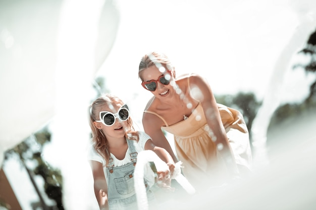 Aproveitando a água. menina e a mãe dela usando óculos escuros, olhando os salpicos de água na fonte.