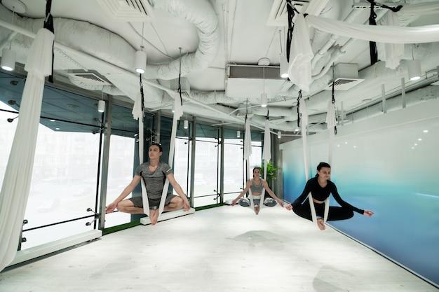 Aproveitando a calma. homem e duas mulheres desfrutando de calma e liberdade enquanto praticam ioga aérea