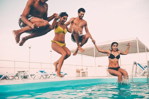 Aproveitando a festa na piscina juntos. grupo de jovens lindos parecendo felizes enquanto pulam na piscina juntos